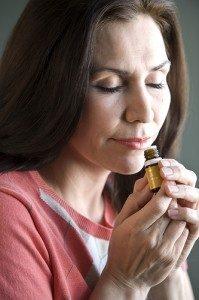 a brunette woman inhaling an essential oil