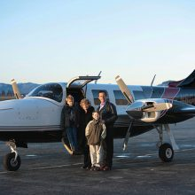Gary Young with family standing next to an airplane