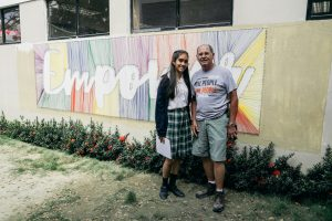 """Two people, a young woman and an older man, stand in front of a wall decorated with the word """"empower."""""""